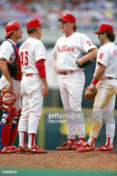 Pitcher Curt Schilling of the Philadelphia Phillies talks on the mound with catcher Darren Daulton pitching coach Johnny Podres and infielder Wally...