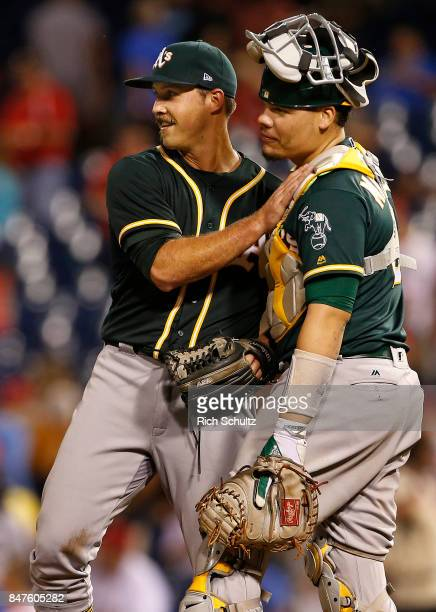 Pitcher Daniel Mengden of the Oakland Athletics is congratulated by Bruce Maxwell after defeating the Philadelphia Phillies 40 and pitching a twohit...