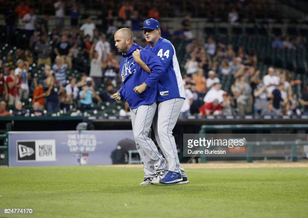 Pitcher Danny Duffy of the Kansas City Royals is held back by assistant hitting coach Brian Buchanan of the Kansas City Royals after Mike Moustakas...