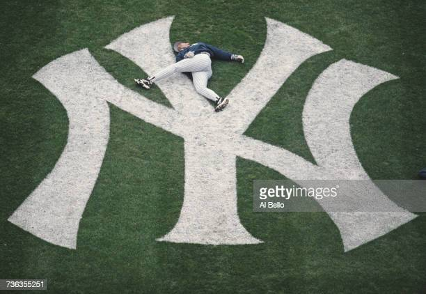 Pitcher David Cone of the New York Yankess goes through his warm up stretching routine on the teams infield logo before the season opening day Major...
