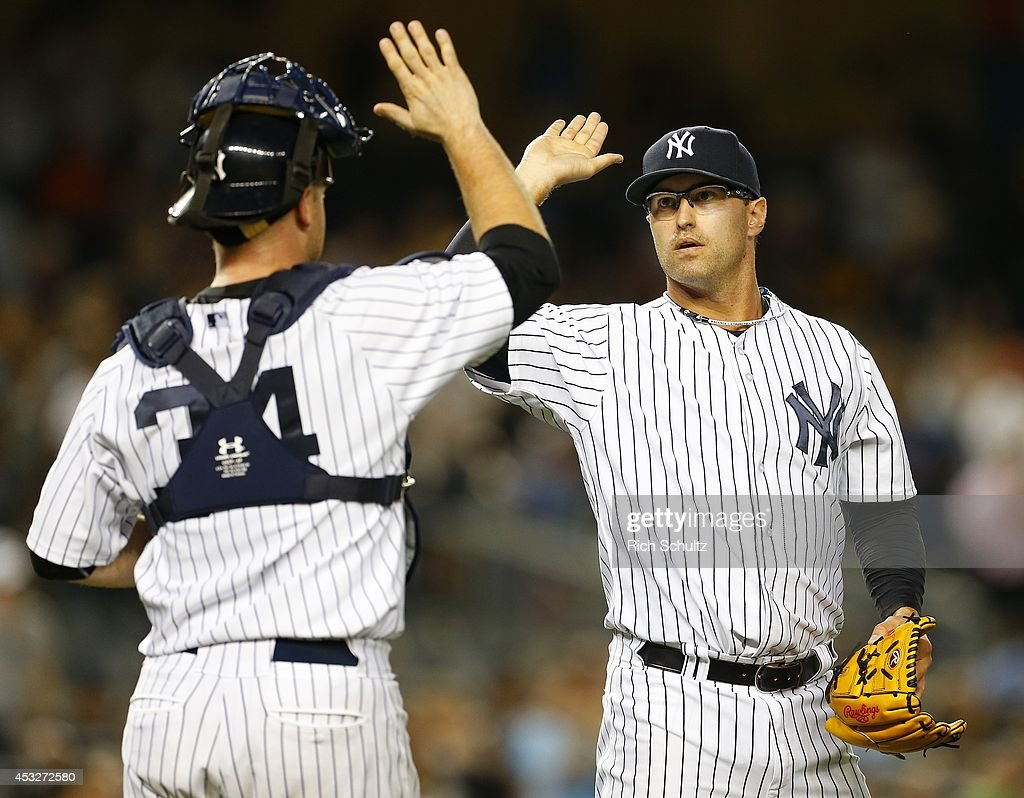 Pitcher David Huff #55 of the New York Yankees is congratulated by catcher Brian McCann #34 after defeating the Detroit Tigers 5-1 in a MLB baseball game at Yankee Stadium on August 6, 2014 in the Bronx borough of New York City.