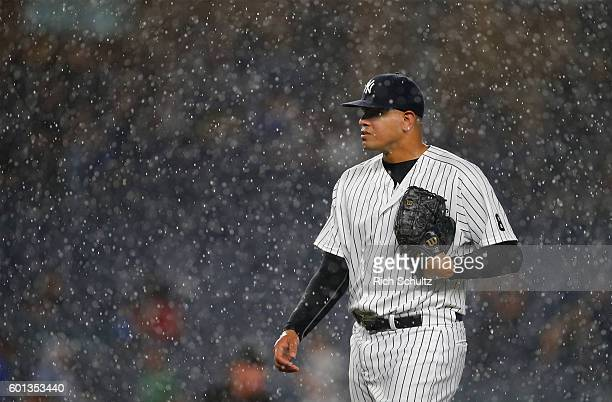 Pitcher Dellin Betances of the New York Yankees walks off the mound as rain pours down causing a rain delay in the ninth inning of a game against the...