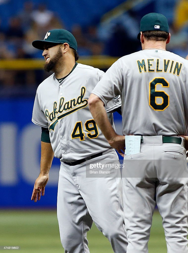 Pitcher Edward Mujica of the Oakland Athletics reacts in pain as manager Bob Melvin looks on after Mujica was injured by a comeback by Bobby Wilson...
