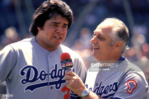 Pitcher Fernando Valenzuela of the Los Angeles Dodgers is interviewed by his manager Tommy Lasorda before the game against the Chicago Cubs on June 7...
