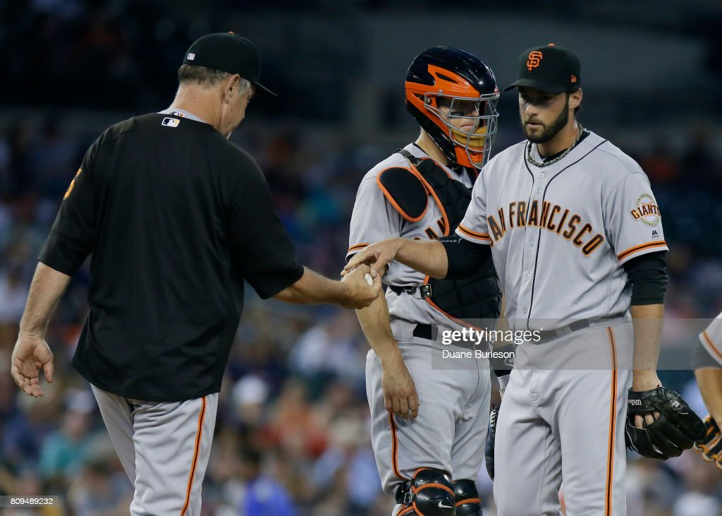 Pitcher George Kontos #70 of the San Francisco Giants is pulled by manager Bruce Bochy #15 of the San Francisco Giants during the seventh inning of a game against the Detroit Tigers as catcher Nick Hundley #5 of the San Francisco Giants looks on at Comerica Park on July 5, 2017 in Detroit, Michigan.
