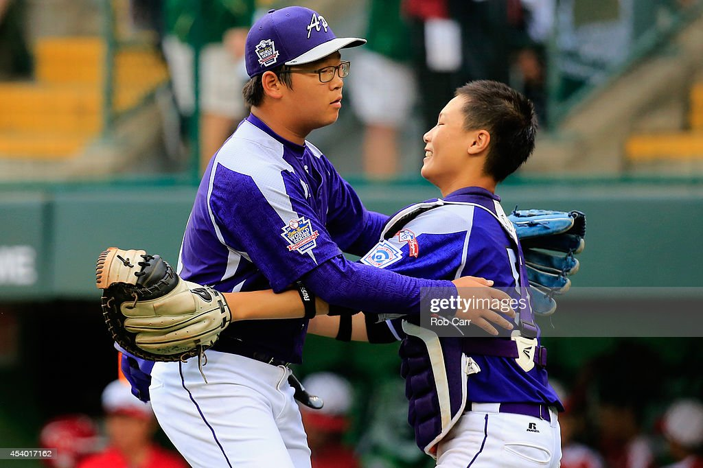 Pitcher Hae Chan Choi #21 and catcher Sang Hoon Han #5 of Team Asia-Pacific celebtrate after defeating Team Japan 12-3 during the International Championship game of the Little League World Series at Lamade Stadium on August 23, 2014 in South Williamsport, Pennsylvania.