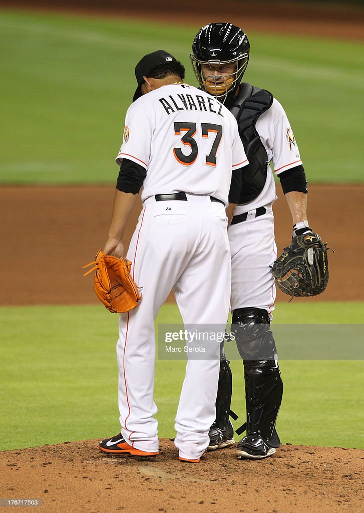 Pitcher <a gi-track='captionPersonalityLinkClicked' href=/galleries/search?phrase=Henderson+Alvarez&family=editorial&specificpeople=7091625 ng-click='$event.stopPropagation()'>Henderson Alvarez</a> #37 of the Miami Marlins chats with Catcher Koyle hill #46 against the San Francisco Giants at Marlins Park on August 17, 2013 in Miami, Florida. The Giants defeated the Marlins 6-4.