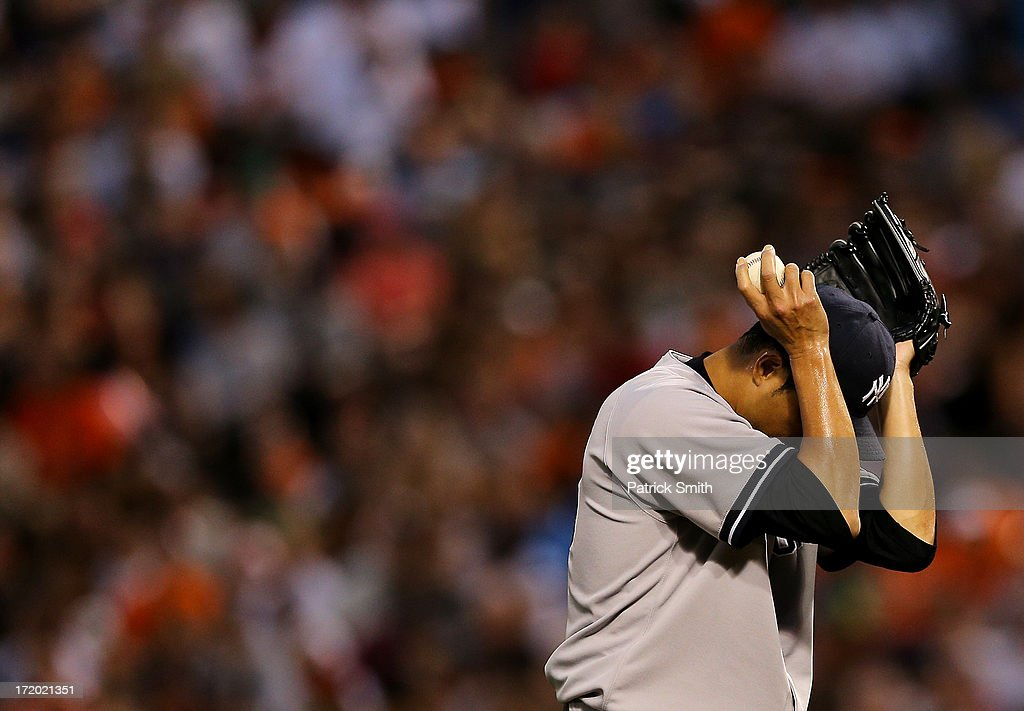Pitcher <a gi-track='captionPersonalityLinkClicked' href=/galleries/search?phrase=Hiroki+Kuroda&family=editorial&specificpeople=5498664 ng-click='$event.stopPropagation()'>Hiroki Kuroda</a> #18 of the New York Yankees wipes sweat from his face against the Baltimore Orioles in the first inning at Oriole Park at Camden Yards on June 30, 2013 in Baltimore, Maryland. The Baltimore Orioles won, 4-2.