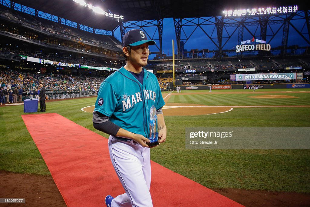 Pitcher <a gi-track='captionPersonalityLinkClicked' href=/galleries/search?phrase=Hisashi+Iwakuma&family=editorial&specificpeople=5723798 ng-click='$event.stopPropagation()'>Hisashi Iwakuma</a> #18 of the Seattle Mariners heads to the dugout after receiving the Most Valuable Pitcher Award prior to the game against the Oakland Athletics at Safeco Field on September 27, 2013 in Seattle, Washington.