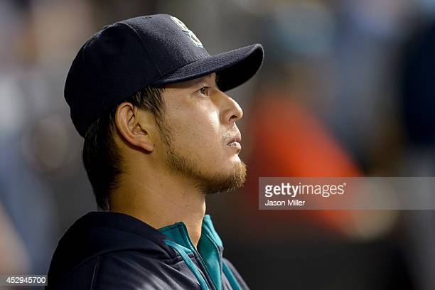 Pitcher Hisashi Iwakuma of the Seattle Mariners watches the game from the dugout during the seventh inning against the Cleveland Indians at...