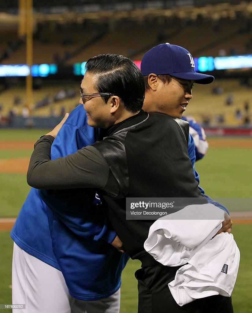 Pitcher Hyun-Jin Ryu #99 of the Los Angeles Dodgers and Korean Pop singer PSY greet one another after the MLB game between the Colorado Rockies and the Los Angeles Dodgers at Dodger Stadium on April 30, 2013 in Los Angeles, California. The Dodgers defeated the Rockies 6-2.