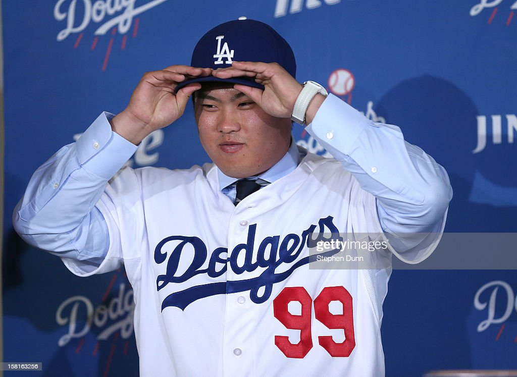 Pitcher Hyun-Jin Ryu puts on his cap and jersey at a press conference introducing him following his signing with the Los Angeles Dodgers at Dodger Stadium on December 10, 2012 in Los Angeles, California.