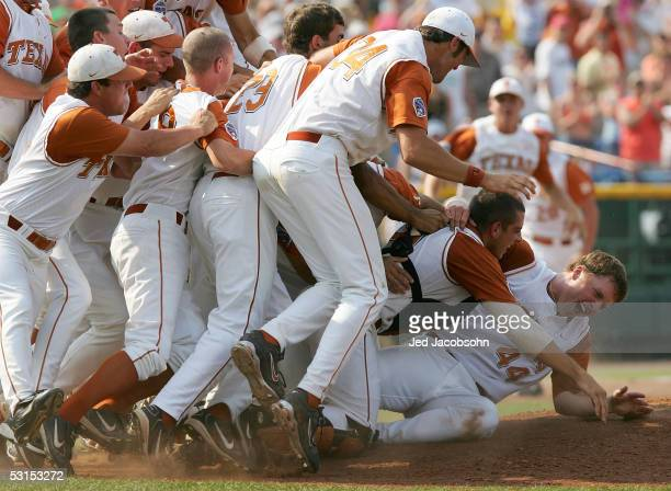 Pitcher J Brent Cox and catcher Taylor Teagarden of the Texas Longhorns are mobbed by teammates after defeating the Florida Gators during Game 2 of...
