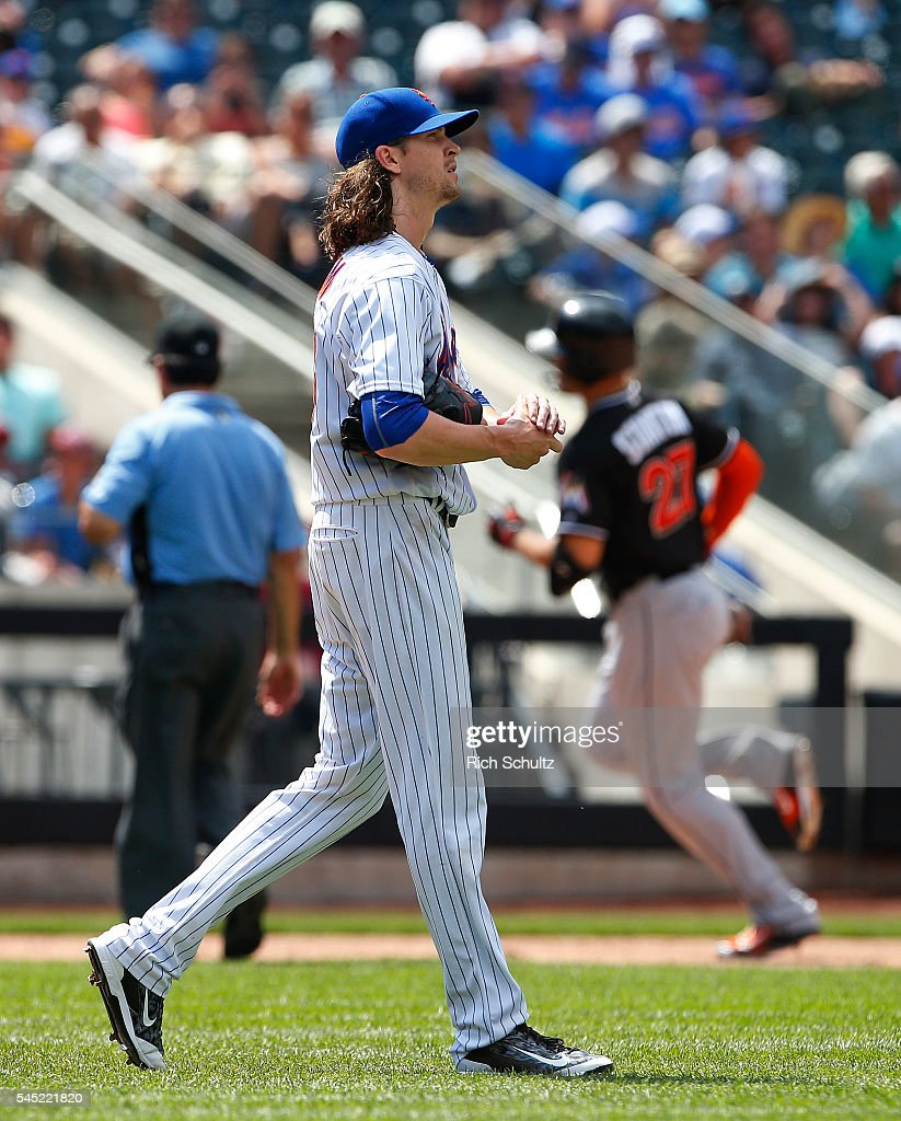 Pitcher Jacob deGrom #48 of the New York Mets rubs a ball as Giancarlo Stanton #27 of the Miami Marlins rounds third base after he hit a home run against the New York Mets in the sixth inning during a game against the New York Mets at Citi Field on July 6, 2016 in the Flushing neighborhood of the Queens borough of New York City.
