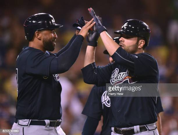 Pitcher Jaime Garcia of the Atlanta Braves celebrates his grand slam homerun with Matt Kemp to take a 90 lead over the Los Angeles Dodgers during the...