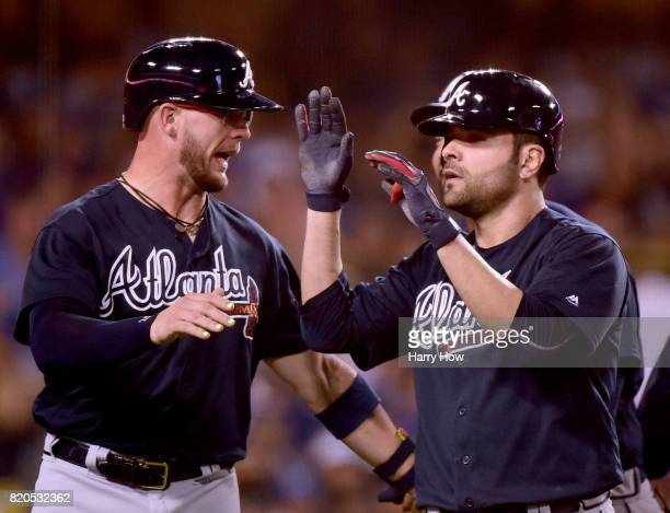 Pitcher Jaime Garcia of the Atlanta Braves celebrates his grand slam homerun with Tyler Flowers to take a 90 lead over the Los Angeles Dodgers during...