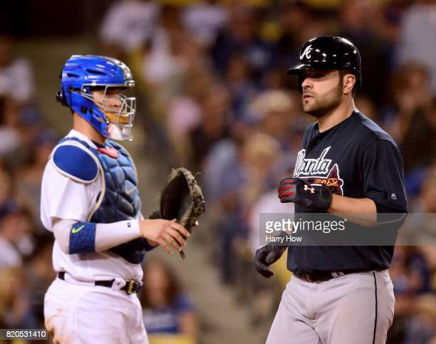 Pitcher Jaime Garcia of the Atlanta Braves scores in front of Yasmani Grandal of the Los Angeles Dodgers after his grand slam homerun to take a 90...