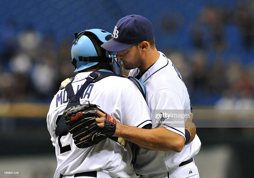 Pitcher Jamey Wright #35 of the Tampa Bay Rays hugs catcher Jose Molina #28 after throwing in relief against the Texas Rangers September 16, 2013 at Tropicana Field in St. Petersburg, Florida. The Rays won 6 - 2.