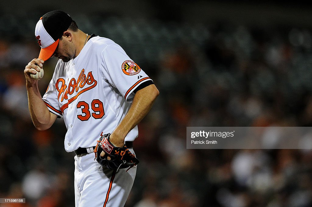 Pitcher Jason Hammel #39 of the Baltimore Orioles dips his hat after giving up a walk in the fifth inning against the Cleveland Indians at Oriole Park at Camden Yards on June 26, 2013 in Baltimore, Maryland. The Cleveland Indians won, 4-3.