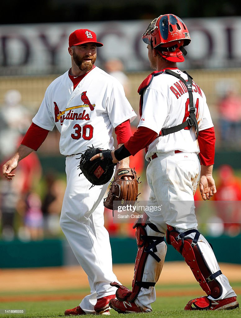 Pitcher Jason Motte #30 of the St. Louis Cardinals celebrates with Bryan Anderson #61 after a game against the Minnesota Twins at Roger Dean Stadium on March 25, 2012 in Jupiter, Florida. The St. Louis Cardinals defeated the Minnesota Twins 9-2.