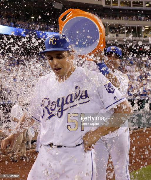 Pitcher Jason Vargas of the Kansas City Royals is doused with a bucket of water by catcher Salvador Perez after pitching a 40 complete game shutout...