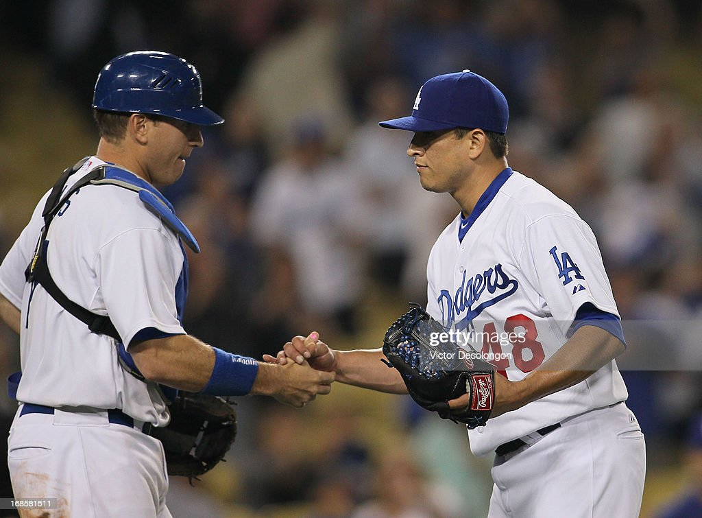 Pitcher Javy Guerra #48 and catcher A.J. Ellis #17 of the Los Angeles Dodgers celebrate after defeating the Miami Marlins 7-1 in their MLB game at Dodger Stadium on May 11, 2013 in Los Angeles, California.