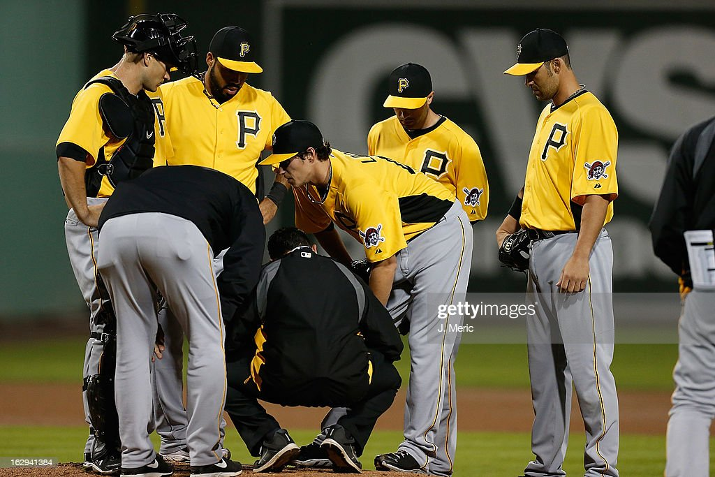 Pitcher Jeff Locke #49 of the Pittsburgh Pirates is examined by the team trainer after he was hit by a ball against the Boston Red Sox during a Grapefruit League Spring Training Game at JetBlue Park on March 1, 2013 in Fort Myers, Florida.