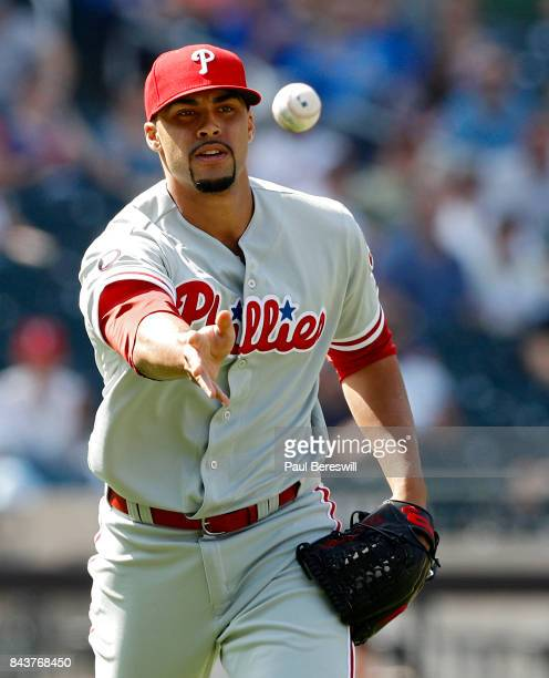 Pitcher Jesen Therrien of the Philadelphia Phillies tosses to first base to get an out in an MLB baseball game against the New York Mets on September...