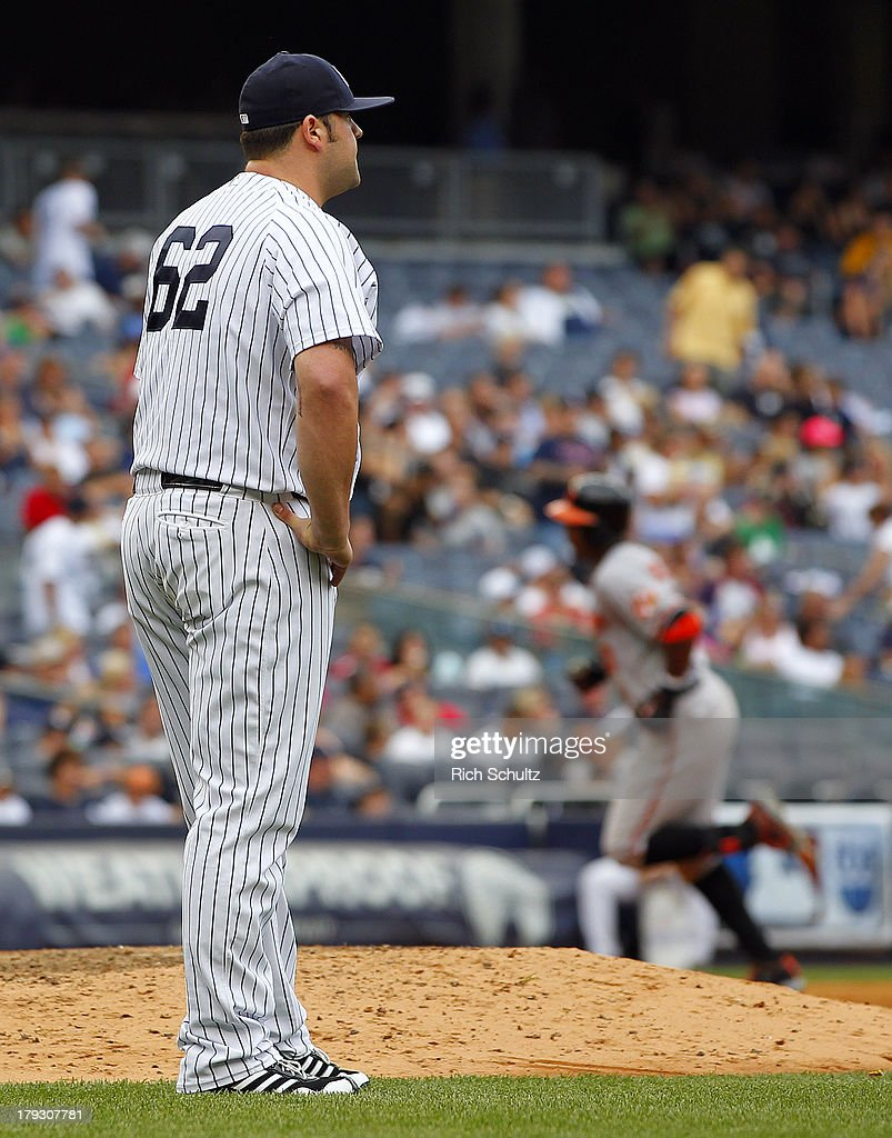 Pitcher Joba Chamberlain #62 of the New York Yankees looks away as Adam Jones #10 of the Baltimore Orioles rounds the bases after hitting a three run home run in the seventh inning in a MLB baseball game at Yankee Stadium on September 1, 2013 in the Bronx borough of New York City.
