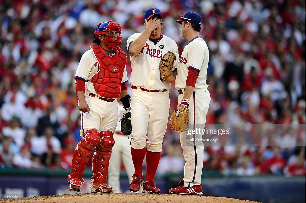 Pitcher <a gi-track='captionPersonalityLinkClicked' href=/galleries/search?phrase=Joe+Blanton+-+Baseball+Player&family=editorial&specificpeople=213055 ng-click='$event.stopPropagation()'>Joe Blanton</a> #56 of the Philadelphia Phillies rubs his head as he talks with catcher <a gi-track='captionPersonalityLinkClicked' href=/galleries/search?phrase=Carlos+Ruiz+-+Baseball+Player&family=editorial&specificpeople=216605 ng-click='$event.stopPropagation()'>Carlos Ruiz</a> #51 (L) and <a gi-track='captionPersonalityLinkClicked' href=/galleries/search?phrase=Chase+Utley&family=editorial&specificpeople=161391 ng-click='$event.stopPropagation()'>Chase Utley</a> #26 against the Colorado Rockies in Game Two of the NLDS during the 2009 MLB Playoffs at Citizens Bank Park on October 8, 2009 in Philadelphia, Pennsylvania.