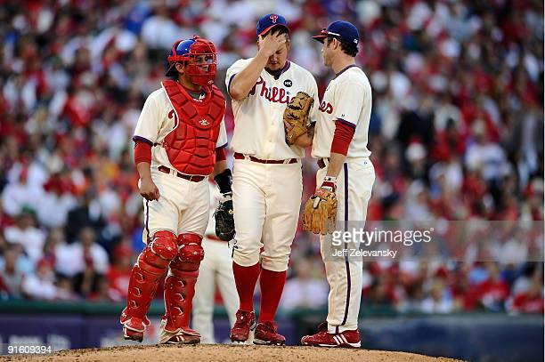 Pitcher Joe Blanton of the Philadelphia Phillies rubs his head as he talks with catcher Carlos Ruiz and Chase Utley against the Colorado Rockies in...