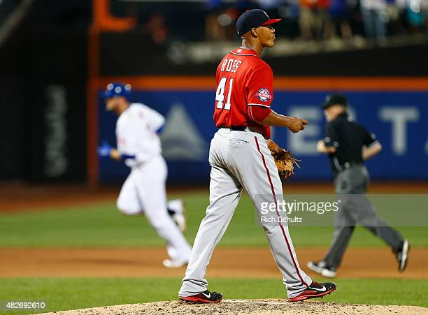 Pitcher Joe Ross of the Washington Nationals looks to the outfield as Lucas Duda of the New York Mets circles the bases after hitting a home run...