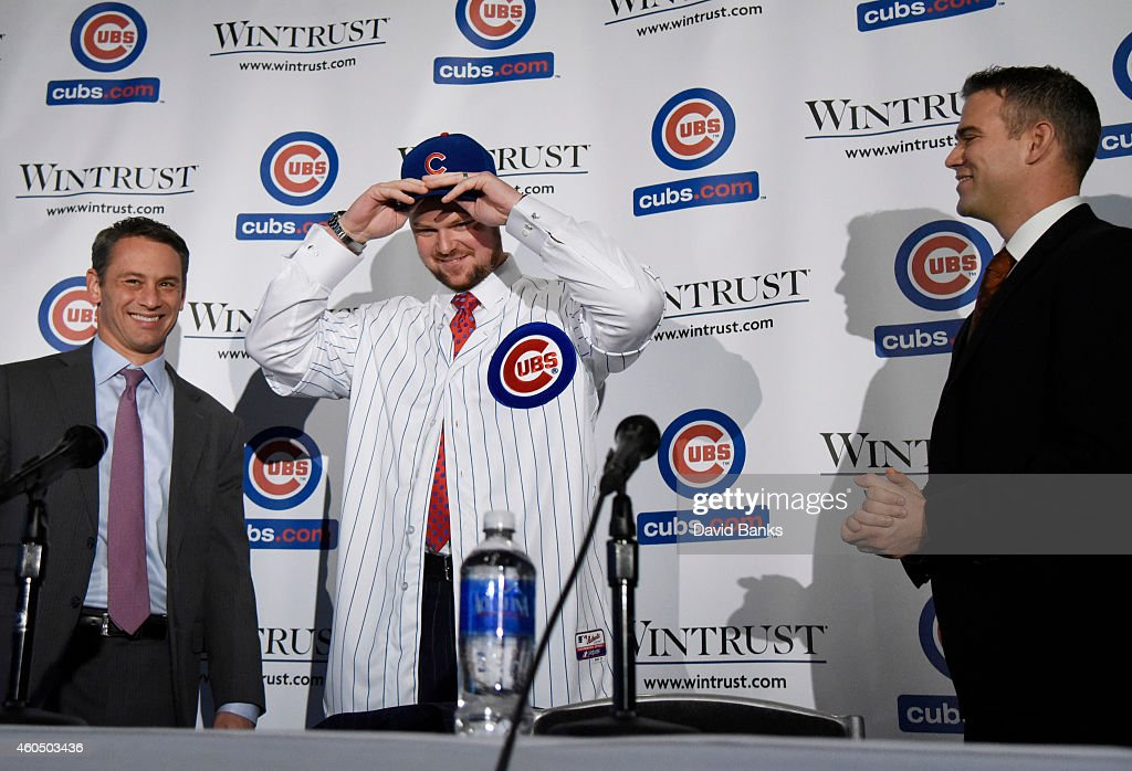 Pitcher Jon Lester (C) puts on a Cubs hat during an introduction press conference as Chicago Cubs President Theo Epstein (R) and general manager Jed Hoyer looks on on December 15, 2014 in Chicago, Illinois.