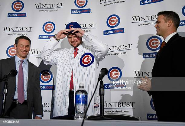 Pitcher Jon Lester puts on a Cubs hat during an introduction press conference as Chicago Cubs President Theo Epstein and general manager Jed Hoyer...