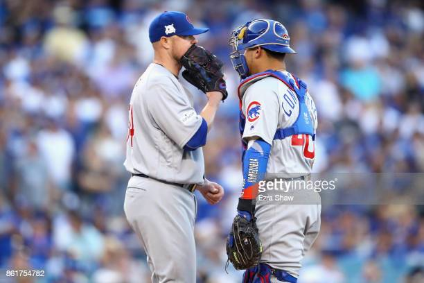Pitcher Jon Lester talks to Willson Contreras of the Chicago Cubs during the third inning of Game Two of the National League Championship Series...