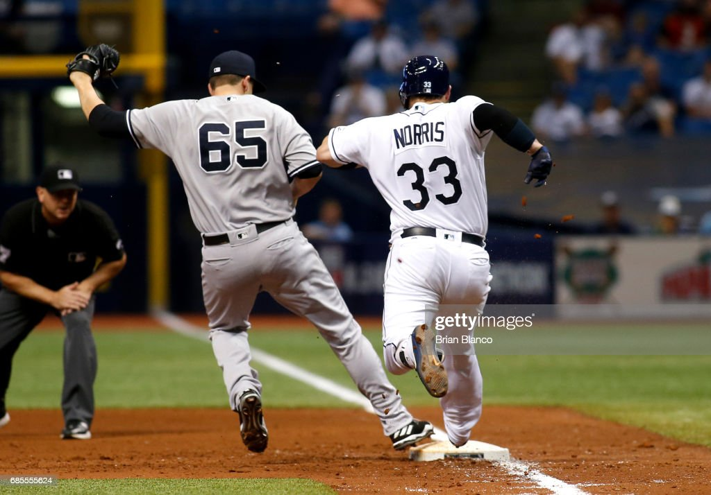 Pitcher Jonathan Holder #65 of the New York Yankees gets the out at first base on Derek Norris #33 of the Tampa Bay Rays to end the sixth inning of a game on May 19, 2017 at Tropicana Field in St. Petersburg, Florida.