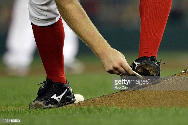 Pitcher Jordan Zimmermann of the Washington Nationals cleans mud off of his cleats between innings against the Cincinnati Reds at Nationals Park on...