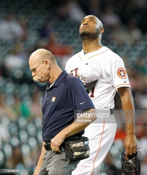 Pitcher Jose Veras of the Houston Astros leaves the game with trainer Rex Jones after taking a comebacker off his hand during action against the...