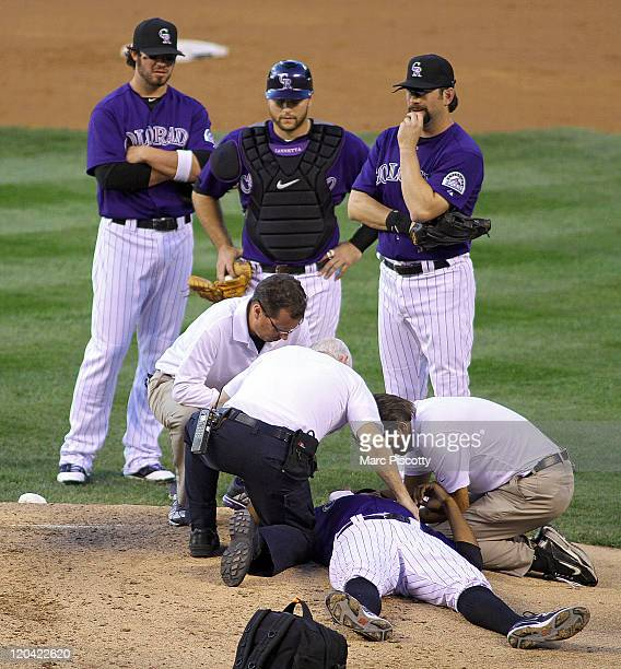 Pitcher Juan Nicasio of the Colorado Rockies is attended to by medical staff on the mound after being hit in the face by a ball while pitching...