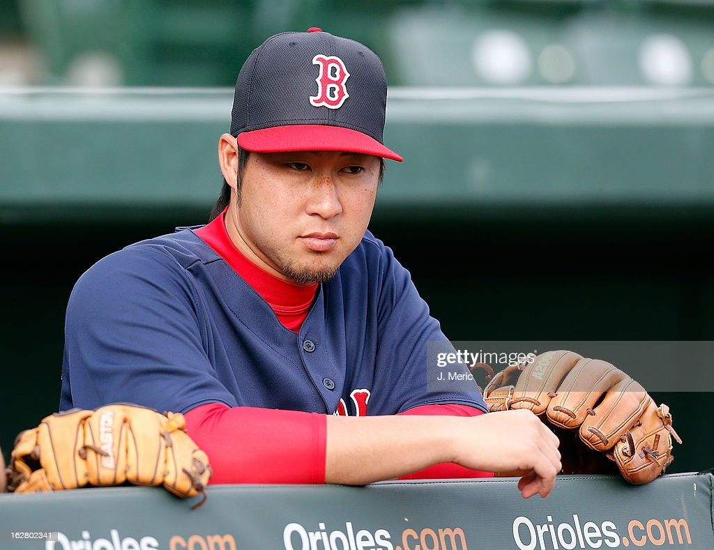 Pitcher Junichi Tazawa #36 of the Boston Red Sox watches as his team warms up just before the start of the Grapefruit League Spring Training Game against the Baltimore Orioles at Ed Smith Stadium on February 27, 2013 in Sarasota, Florida.