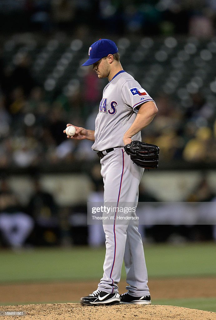 Pitcher <a gi-track='captionPersonalityLinkClicked' href=/galleries/search?phrase=Justin+Grimm&family=editorial&specificpeople=9480126 ng-click='$event.stopPropagation()'>Justin Grimm</a> #51 of the Texas Rangers stands on the mound staring at the ball while he waits for manager Ron Washington to come take him out of the game against the Oakland Athletics in the six inning at O.co Coliseum on May 13, 2013 in Oakland, California.