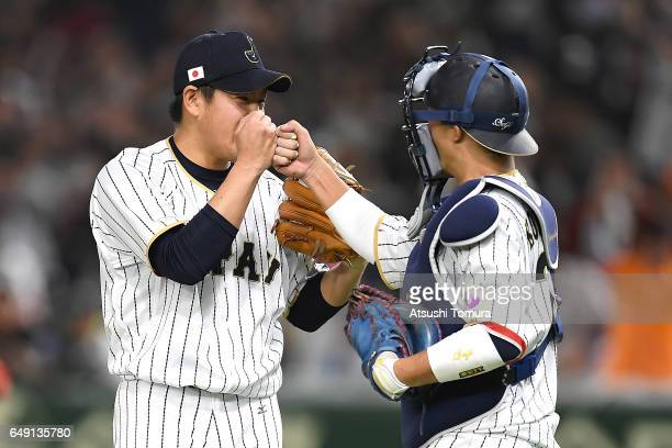 Pitcher Kazuhisa Makita of Japan celebrates with catcher Seiji Kobayashi of Japan after winning the World Baseball Classic Pool B Game One between...