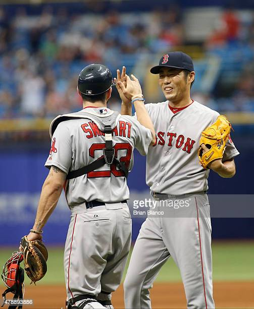 Pitcher Koji Uehara of the Boston Red Sox and catcher Blake Swihart celebrate their 52 win over the Tampa Bay Rays at the end of a game on June 28...