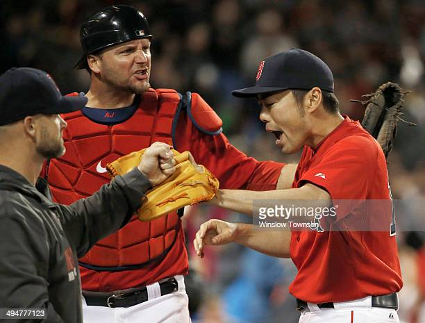Pitcher Koji Uehara of the Boston Red Sox is congratulated by catchers David Ross and AJ Pierzynski after retiring the Tampa Bay Rays in the ninth...