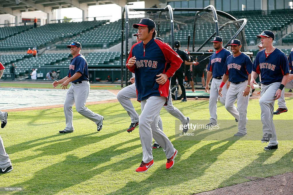 Pitcher Koji Uehara #19 of the Boston Red Sox warms up just before the start of the Grapefruit League Spring Training Game against the Baltimore Orioles at Ed Smith Stadium on February 27, 2013 in Sarasota, Florida.