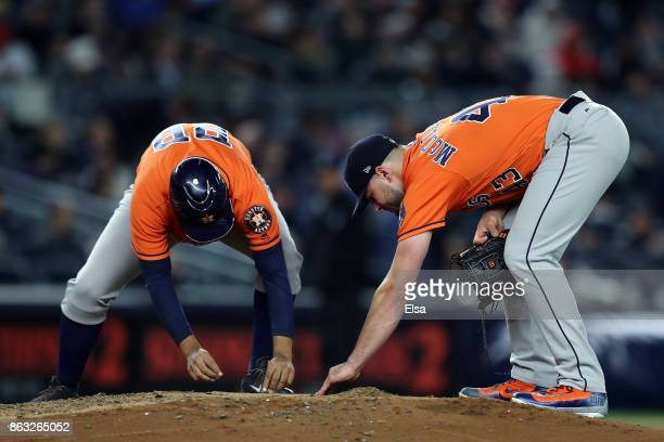 Pitcher Lance McCullers Jr #43 of the Houston Astros looks for a piece of jewlery that he lost on the mound while pitching against the New York...