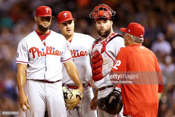 Pitcher Luis Garcia of the Philadelphia Phillies waits on the mound with first baseman Tommy Joseph and catcher Cameron Rupp for pitching coach Bob...