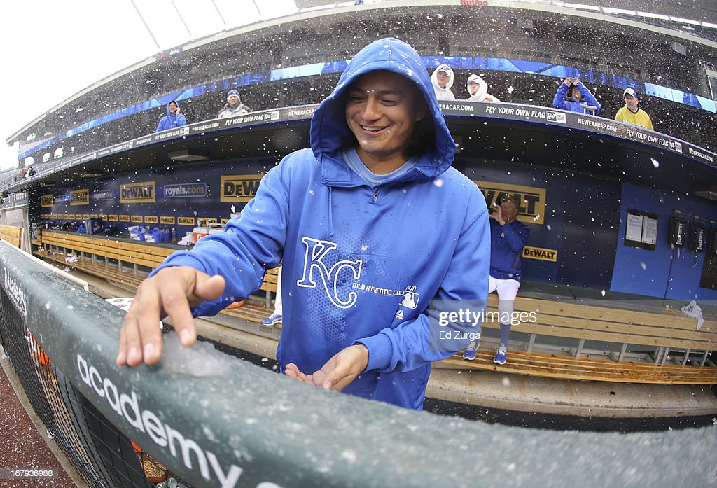 Pitcher Luis Mendoza #39 of the Kansas City Royals scoops up snow from the dugout rail during a delay in play against the Tampa Bay Rays at Kauffman Stadium on May 2, 2013 in Kansas City, Missouri. The game was postponed due to weather.