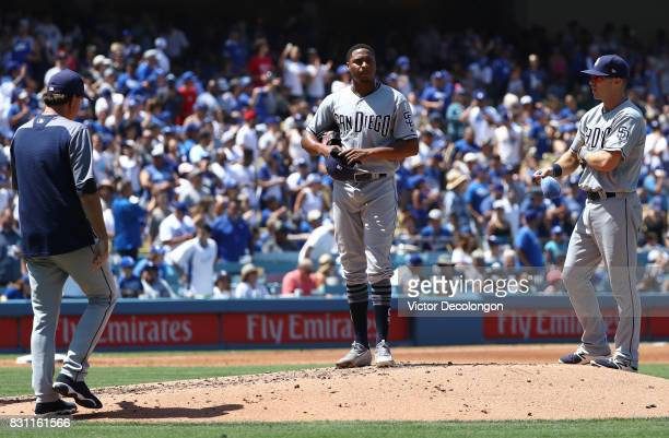 Pitcher Luis Perdomo of the San Diego Padres looks on with teammate Dusty Coleman as pitching coach Don Balsley approaches the mound after Perdomo...