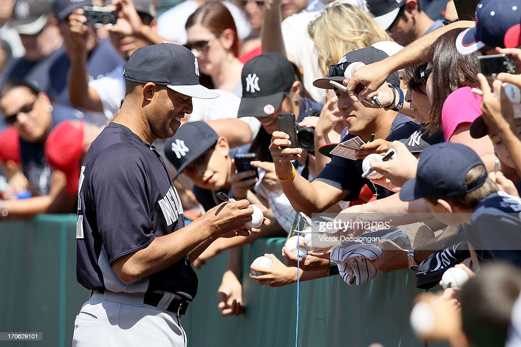 Pitcher Mariano Rivera #42 of the New York Yankees signs autographs for fans prior to the MLB game against the Los Angeles Angels of Anaheim at Angel Stadium of Anaheim on June 15, 2013 in Anaheim, California.